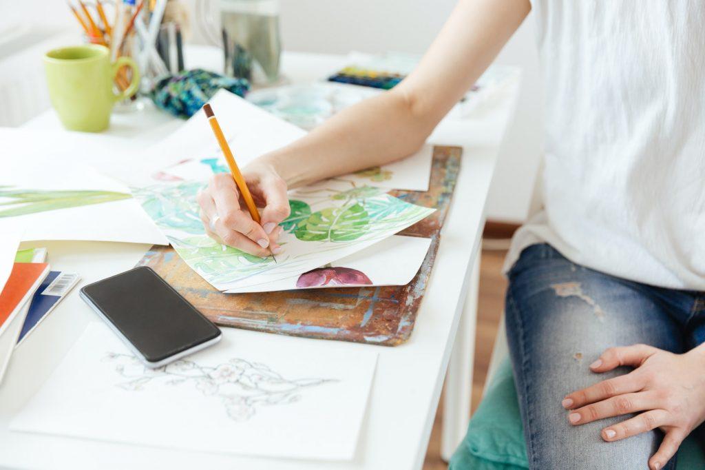 Woman painter drawing in art studio